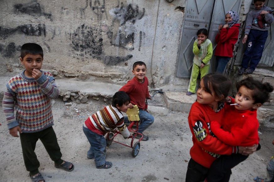 epa05184000 Syrian children play outside their home at the rebel-held neighborhood of Tishreen, after a ceasefire that went into effect in Damascus, Syria, 27 February 2016. According to monitoring group, the ceasefire in Syria was largely holding on 27 February hours after the deal brokered by Russia and the United States went into effect. The Syrian government and 97 rebel and militant groups have agreed on the truce that went into effect at midnight 26 February (2200 GMT) without including the Islamic State militant group or the al-Nusra Front, an al-Qaida affiliate in Syria.  EPA/MOHAMMED BADRA