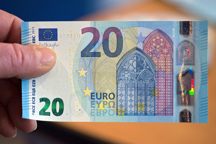 epa05010541 An employee of the German Federal Bank (Bundesbank) holds up a new 20 euro note in Duesseldorf, Germany, 04 November 2015. The new 20 euro note will be put into circulation starting 25 November 2015.  EPA/FEDERICO GAMBARINI