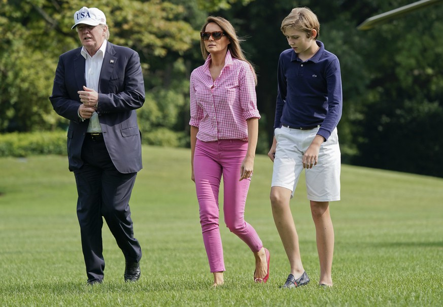 President Donald Trump, first lady Melania Trump and their son Barron Trump, 11, walk across the South Lawn of the White House in Washington, Sunday, Aug. 27, 2017, following their return after spending the weekend at nearby Camp David, Md., (AP Photo/Pablo Martinez Monsivais)