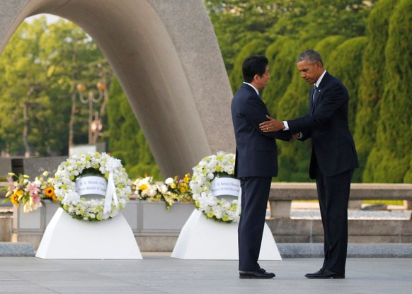 U.S. President Barack Obama (R) puts his arm around Japanese Prime Minister Shinzo Abe after they laid wreaths in front of a cenotaph at Hiroshima Peace Memorial Park in Hiroshima, Japan May 27, 2016. REUTERS/Carlos Barria     TPX IMAGES OF THE DAY