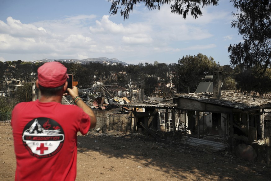A member of a rescue team takes a photography the burned houses in Mati, east of Athens, Wednesday, July 25, 2018. Rescue crews were searching Wednesday through charred homes and cars for those still missing after the deadliest wildfires to hit Greece in decades decimated seaside areas near Athens, killing at least 79 people and sending thousands fleeing. (AP Photo/Thanassis Stavrakis)