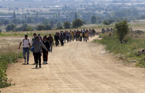 Migrants walk from the Macedonian border into Serbia, near the village of Miratovac, Serbia, Monday, Aug. 24, 2015. The more than 5,000 migrants who reached Serbia overnight faced an overcrowded refugee center where they have to apply for asylum — the paper that allows them three days to reach Hungary. (AP Photo/Darko Vojinovic)