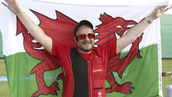 Michael Wixey of Wales celebrates with his national flag after he won the gold medal during the men's trap final at the Belmont Shooting Centre during the 2018 Commonwealth Games in Brisbane, Australia, Saturday, April 14, 2018. (AP Photo/Tertius Pickard)
