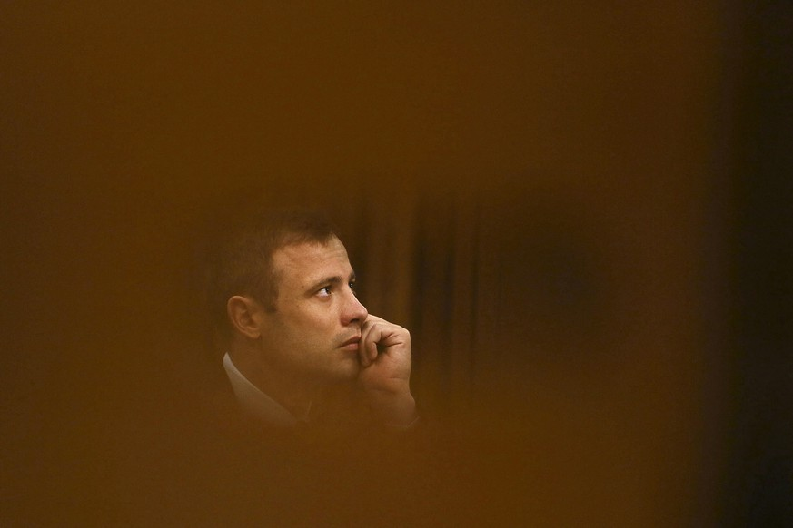 FILE - In this Thursday, Oct. 16, 2014 file photo Oscar Pistorius sits in the high court for the fourth day of sentencing in Pretoria, South Africa. Pistorius is expected to be released Friday, Aug. 21, 2015 after being locked up for ten months for killing his girlfriend in 2013. He will go into house arrest to serve the rest of his five year sentence.  (AP Photo/Alon Skuy, Pool, File))