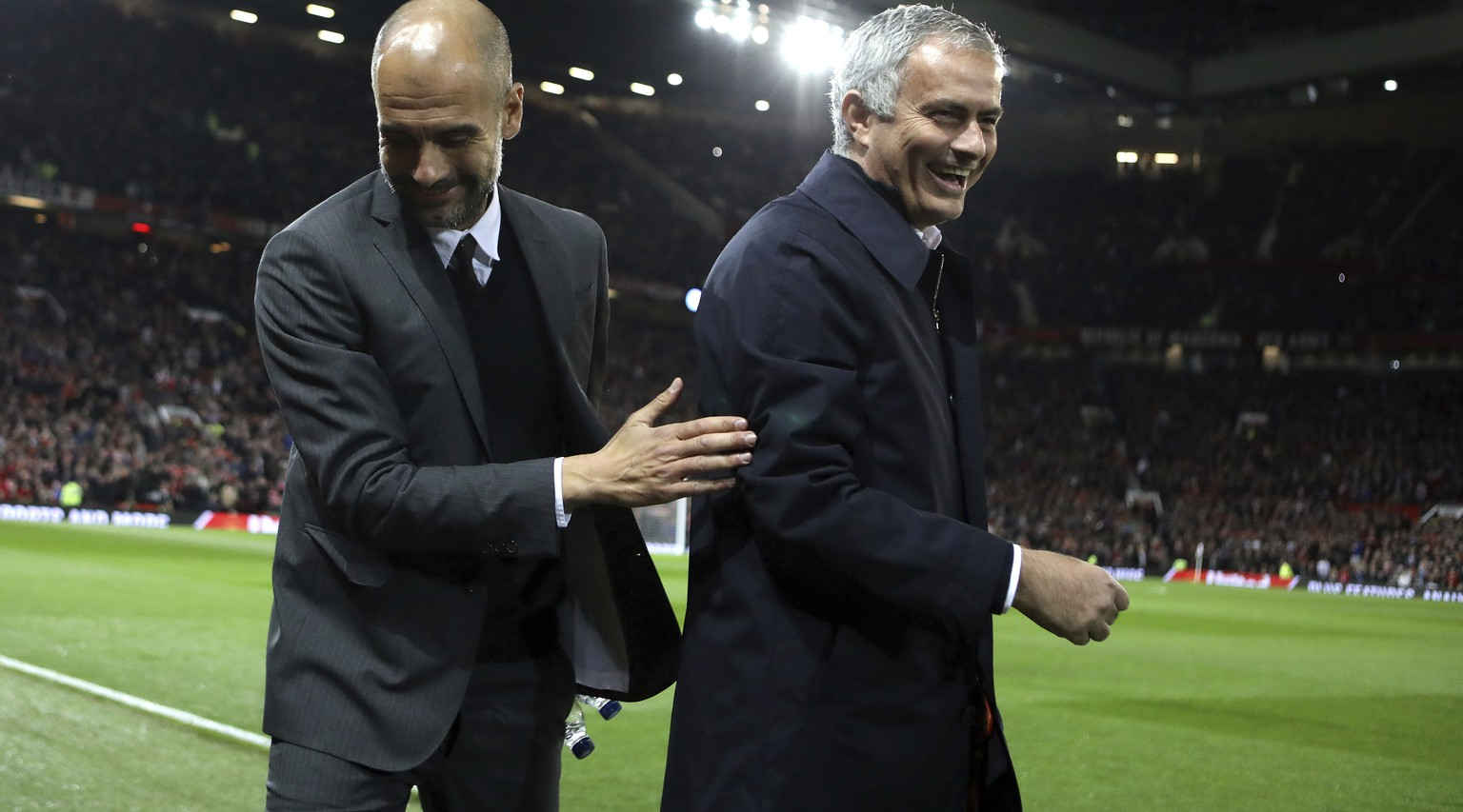 Manchester City's manager Pep Guardiola, left, and Manchester United's manager Jose Mourinho smile ahead of the English League Cup soccer match between Manchester United and Manchester City at Old Trafford stadium in Manchester, Wednesday, Oct. 26, 2016. (AP Photo/Dave Thompson)