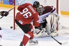 Latvia's goaltender Edgars Masalskis, right, fights for the puck against Switzerland's forward Damien Brunner, left, during the men's preliminary Group C game between Switzerland and Latvia at the XXII Winter Olympics 2014 Sochi in Sochi, Russia, on Wednesday, February 12, 2014. (KEYSTONE/Laurent Gillieron)