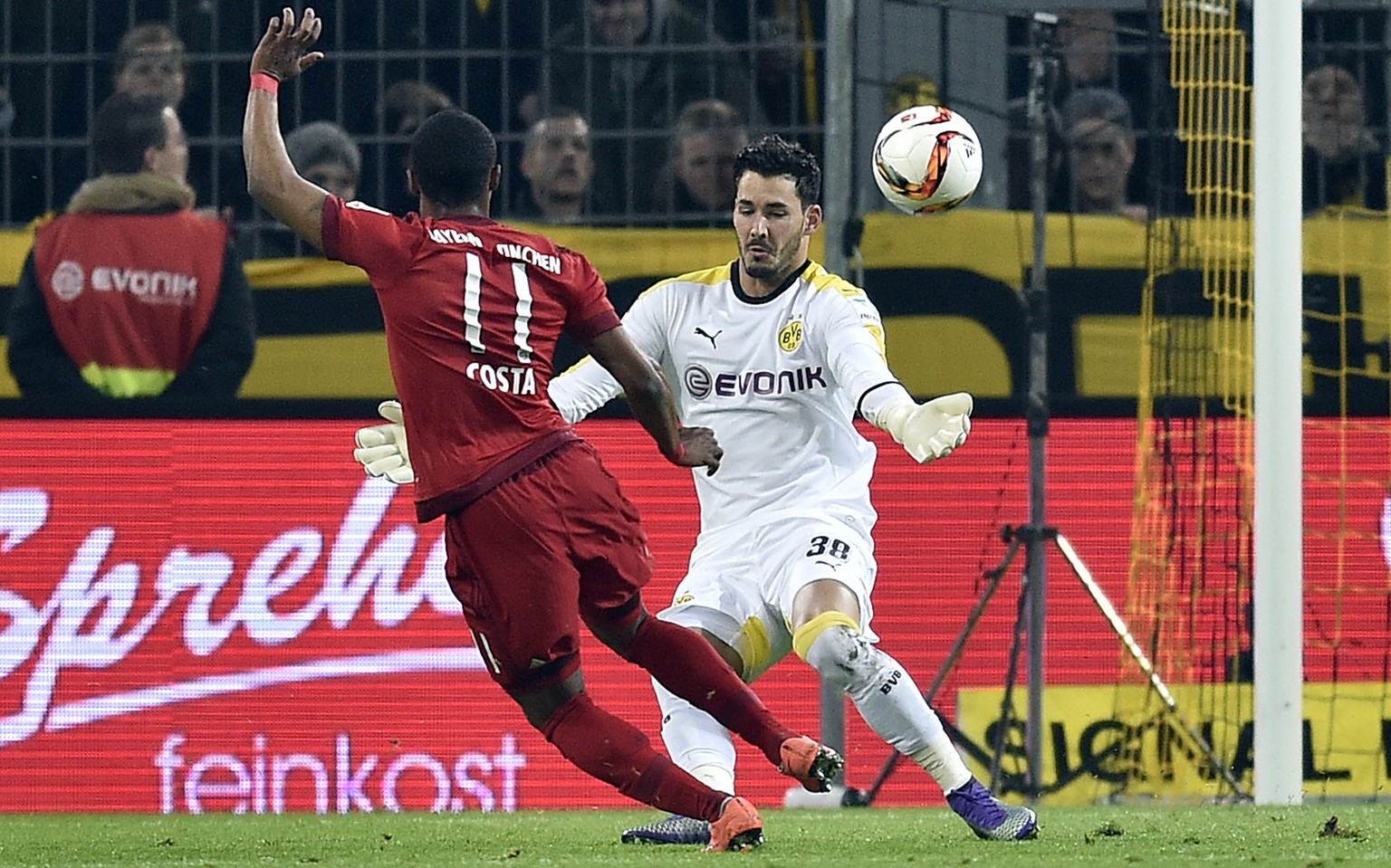 Dortmund's goalkeeper Roman Buerki, right, catches a ball from Bayern's Douglas Costa during the German Bundesliga soccer match between Borussia Dortmund and Bayern Munich, in Dortmund, Germany, Saturday, March 5, 2016. (AP Photo/Martin Meissner)