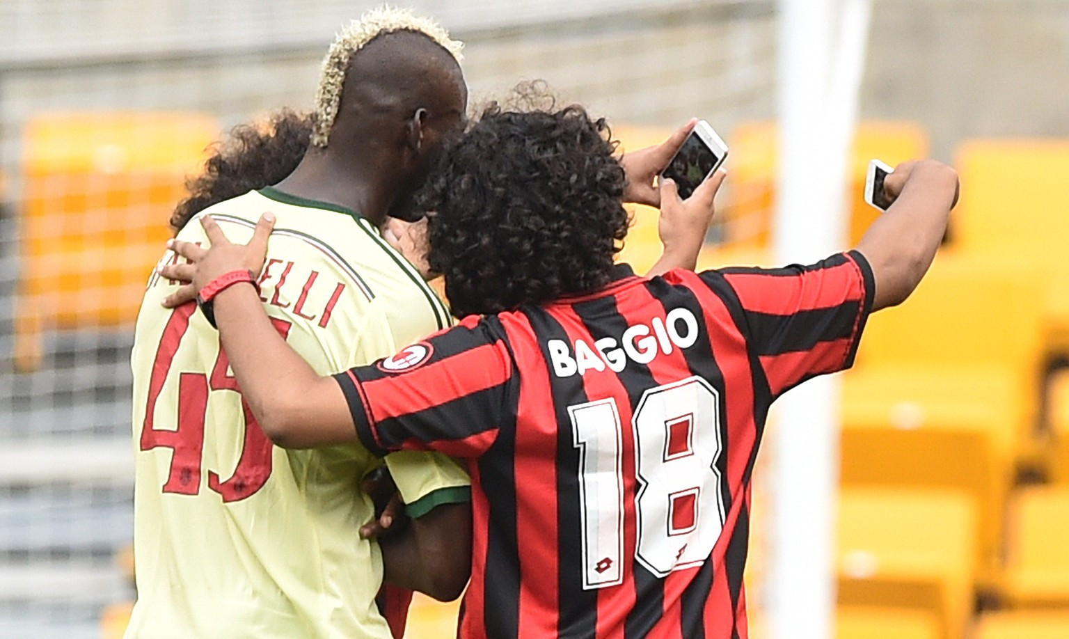 Two fans take selfies with AC Milan's Mario Balotelli after running on the pitch during a Champions Cup match against Manchester City at Heinz Field in Pittsburgh on July 27, 2014. Manchester City won 5-1.   AFP PHOTO/Nicholas KAMM