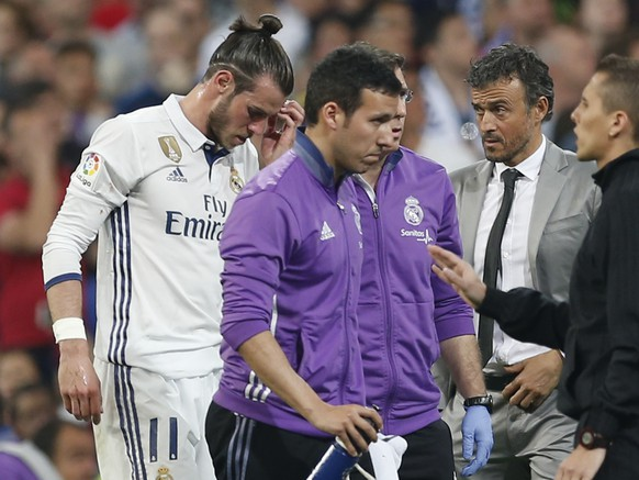Real Madrid's Gareth Bale leaves the field of play after being injured, as Barcelona's head coach Luis Enrique looks on during a Spanish La Liga soccer match between Real Madrid and Barcelona, dubbed 'el clasico', at the Santiago Bernabeu stadium in Madrid, Spain, Sunday, April 23, 2017. (AP Photo/Francisco Seco)