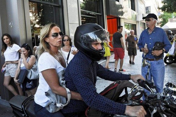 epa04833707 Greece's former Finance Minister Yanis Varoufakis drives his motorcyle with his wife Danae Stratou after exiting the Finance Ministry in Athens, Greece, 05 July 2015. Greece's Finance Minister Yanis Varoufakis said on 06 July he is resigning, making the announcement in a tweet and on his personal webpage. The announcement came hours after the ballot count of the referendum on Greece's bailout package was completed.  EPA/FOTIS PLEGAS G.  EPA/FOTIS PLEGAS G.