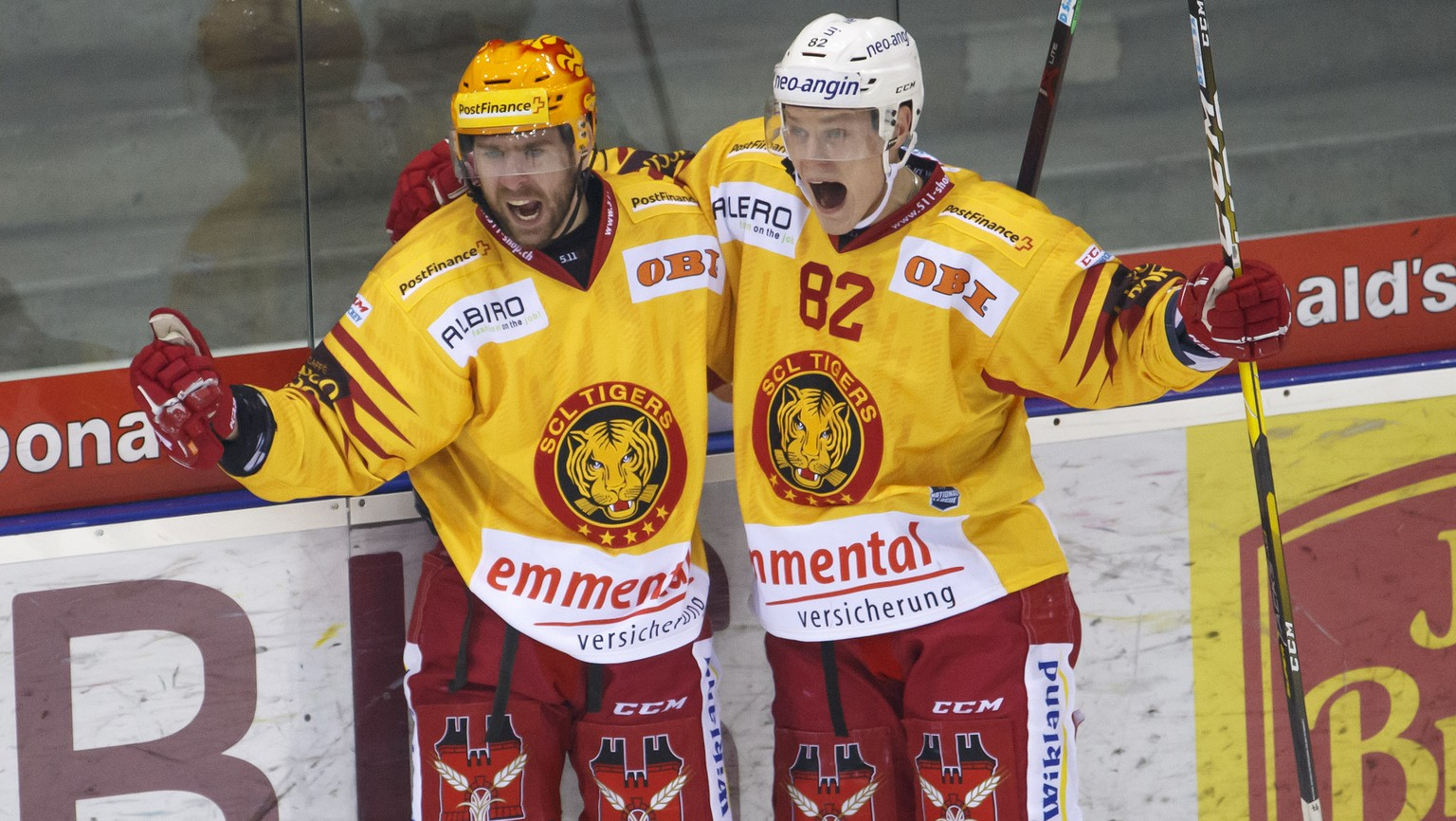Tiger's forward Christopher DiDomenico, of Canada, left, celebrates his goal with teammates forward Harri Pesonen, of Finland, right, after scoring the 3:5, during a National League regular season game of the Swiss Championship between Geneve-Servette HC and SCL Tigers, at the ice stadium Les Vernets, in Geneva, Switzerland, Friday, February 8, 2019. (KEYSTONE/Salvatore Di Nolfi)