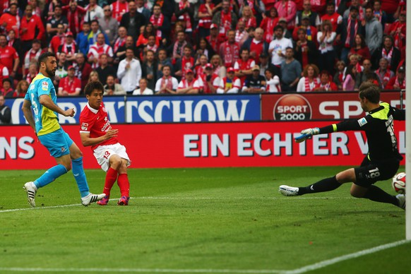 MAINZ, GERMANY - MAY 16: Ja-Cheol Koo of Mainz scores his team's first goal against goalkeeper Thomas Kessler and Dominic Maroh of Koeln during the Bundesliga match between 1. FSV Mainz 05 and 1. FC Koeln at Coface Arena on May 16, 2015 in Mainz, Germany.  (Photo by Alex Grimm/Bongarts/Getty Images)