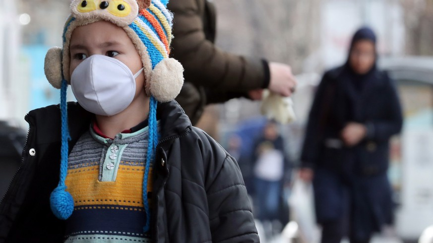 epa08250952 An Iranian child wearing face mask walks on a street of Tehran, Iran, 26 February 2020. According to the Ministry of Health, 139 people diagnosed with the Covid-19 coronavirus and 19 people have died in Iran.  EPA/ABEDIN TAHERKENAREH
