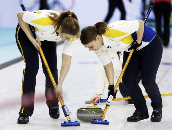 Sweden's third Christina Bertrup (L) and second Maria Wennerstroem sweep during their women's curling round robin game against Switzerland at the Sochi 2014 Winter Olympic Games in the Ice Cube Curling Center February 13, 2014. REUTERS/Ints Kalnins (RUSSIA  - Tags: SPORT OLYMPICS SPORT CURLING)