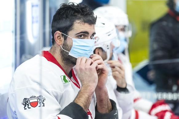 Lausannes Mark Barberio zieht eine Atemschutzmaske an im Eishockey Spiel der National League zwischen dem EV Zug und Lausanne HC am Dienstag, 15. Dezember 2020, in der Bossard Arena in Zug. (KEYSTONE/Alexandra Wey)