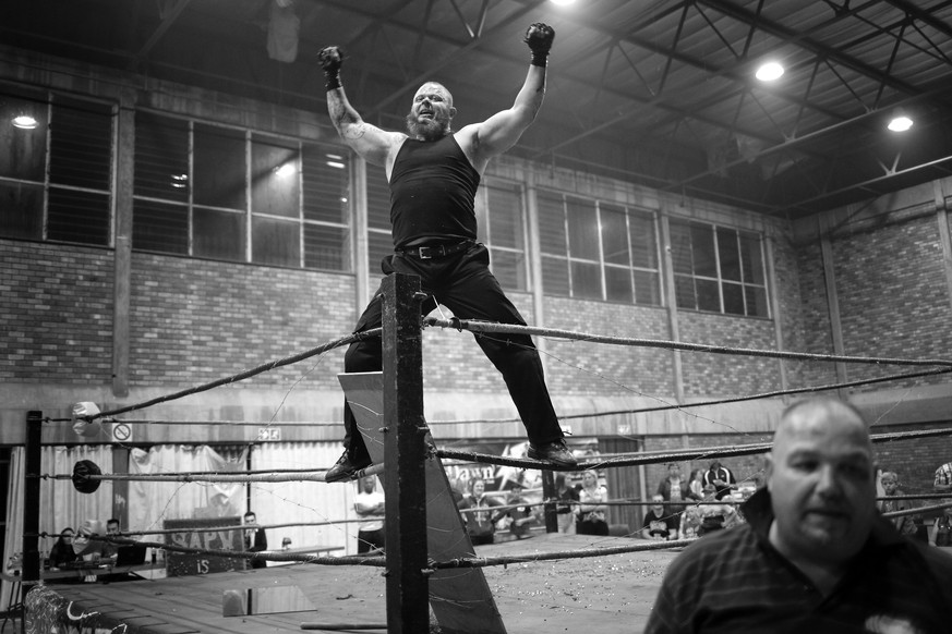epa05916687 (25/32) Wrestler 'The Jackal' climbs onto the ropes to celebrate beating 'Hector Payne' during a hardcore wrestling match at the Brakpan Community Hall, in Brakpan, Johannesburg, South Africa, 04 March 2017. In the East Rand region of South Africa lives dedicated, passionate, amateur hardcore wrestling community, whose members find time between work and family to put on shows for their devoted following of fans at local community halls, high schools and motorcycle rallies. Hardcore wrestling is a form of professional wrestling where disqualifications, count-outs, and all other different rules do not apply. Matches are decided with the use of numerous dangerous items including tables, chairs, barbed wire, light tubes, shovels, chains, hammers, etc.  EPA/KIM LUDBROOK ATTENTION EDITORS: PICTURE CONVERTED TO BLACK AND WHITE ++ PLEASE REFER TO ADVISORY NOTICE (epa05916662) FOR FULL PHOTO ESSAY TEXT