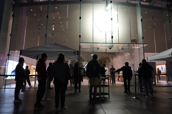 Shoppers wait outside an Apple Store on Thursday, Nov. 19, 2020, in Santa Monica, Calif. California Gov. Gavin Newsom is imposing an overnight curfew as the most populous state tries to head off a surge in coronavirus cases. On Thursday, Newsom announced a limited stay-at-home order effective Saturday night in 41 counties that account for more than 90 percent of the state's population. (AP Photo/Marcio Jose Sanchez)