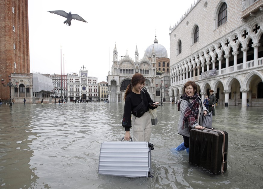 Tourists push their luggage in a flooded St. Mark's Square, in Venice, Wednesday, Nov. 13, 2019. The high-water mark hit 187 centimeters (74 inches) late Tuesday, Nov. 12, 2019, meaning more than 85% of the city was flooded. The highest level ever recorded was 194 centimeters (76 inches) during infamous flooding in 1966. (AP Photo/Luca Bruno)