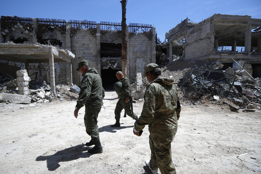Russian military police officers check a weapons factory left behind by members of the Army of Islam group, in the town of Douma, the site of a suspected chemical weapons attack, near Damascus, Syria, Monday, April 16, 2018. Faisal Mekdad, Syria's deputy foreign minister, said on Monday that his country is