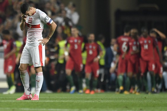 epa06257657 Switzerland's Granit Xhaka, left, reacts while the Portuguese players celebrate their second goal during the 2018 Fifa World Cup Russia group B qualification soccer match between Portugal and Switzerland at the Estadio da Luz stadium, in Lisbon, Portugal, Tuesday, October 10, 2017.  EPA/LAURENT GILLIERON