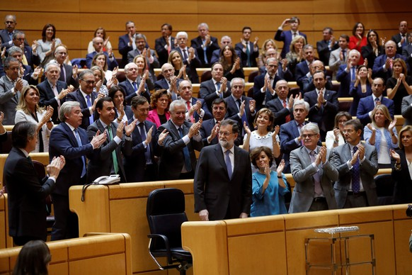 epa06292143 Spanish Prime Minister, Mariano Rajoy (C), receives the applause of the members of his Government after delivering his speech during the Senate's extraordinary plenary session on the application of Article 155 of the Spanish Constitution, in Madrid, Spain, on 27 October 2017. Rajoy has spoken before the Senate to defend the Government's measures for the establishment of the Article 155, a day after Catalan President, Carles Puigdemont, confirmed that he will not call regional elections. Paralelly, the Catalan Parliament is to continue a plenary session to debate whether to declare an uniteral declaration of independence and the proclamation of a republic in Catalonia.  EPA/CHEMA MOYA