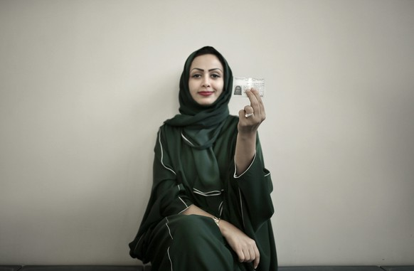 In this June 23, 2018 photo, 34-year old Asmaa al-Assdmi poses for a photograph holding her new car license at the Saudi Driving School inside Princess Nora University in Saudi Arabia. (AP Photo/Nariman El-Mofty)