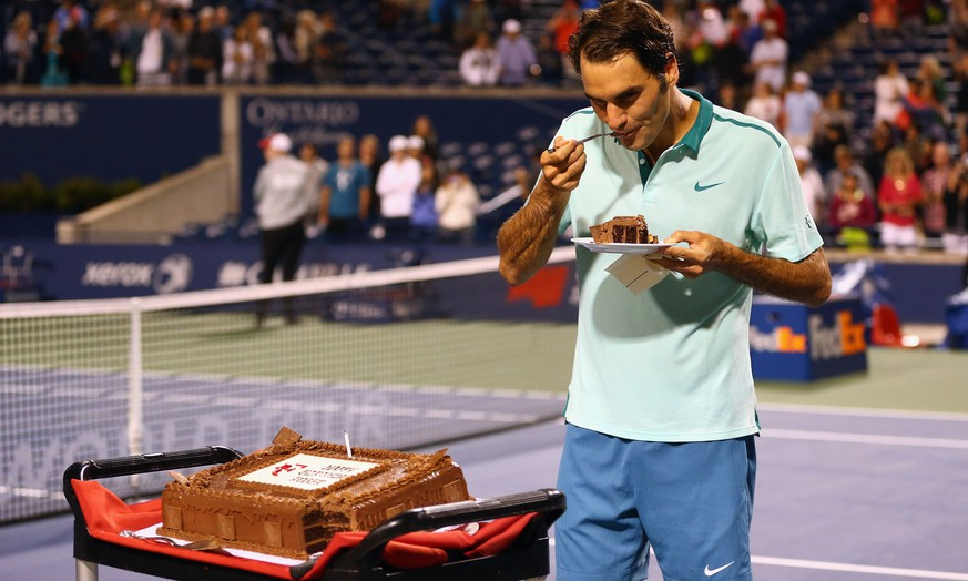 TORONTO, ON - AUGUST 08: Roger Federer of Switzerland has a piece of his birthday cake after a quarterfinals win against David Ferrer of Spain during Rogers Cup at Rexall Centre at York University on August 8, 2014 in Toronto, Canada.   Ronald Martinez/Getty Images/AFP == FOR NEWSPAPERS, INTERNET, TELCOS & TELEVISION USE ONLY ==