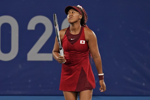 Naomi Osaka, of Japan, reacts after losing a point to Marketa Vondrousova, of the Czech Republic, during the third round of the tennis competition at the 2020 Summer Olympics, Tuesday, July 27, 2021, in Tokyo, Japan. (AP Photo/Seth Wenig) Naomi Osaka