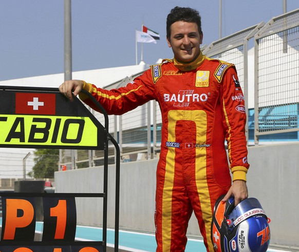 Swiss GP2 racing driver Fabio Leimer poses for photographers at the Yas Marina racetrack in Abu Dhabi, United Arab Emirates, Sunday, Nov. 3, 2013. Leimer secured the GP2 Drivers' Championship title in the Saturday race here. (AP Photo)