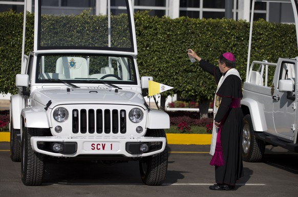 Papal Nuncio Christophe Pierre sprinkles holy water onto popemobiles that will be used during Pope Francis' upcoming visit, inside the presidential hangar at Mexico City's airport, Monday, Feb. 8, 2016. Two popemobiles built on Jeep frames were brought from the United States, while three popemobiles adapted from Ram pick-up trucks were built in Mexico. The Pope requested open-air vehicles without bullet-proof windows for his trip to Mexico. (AP Photo/Rebecca Blackwell)