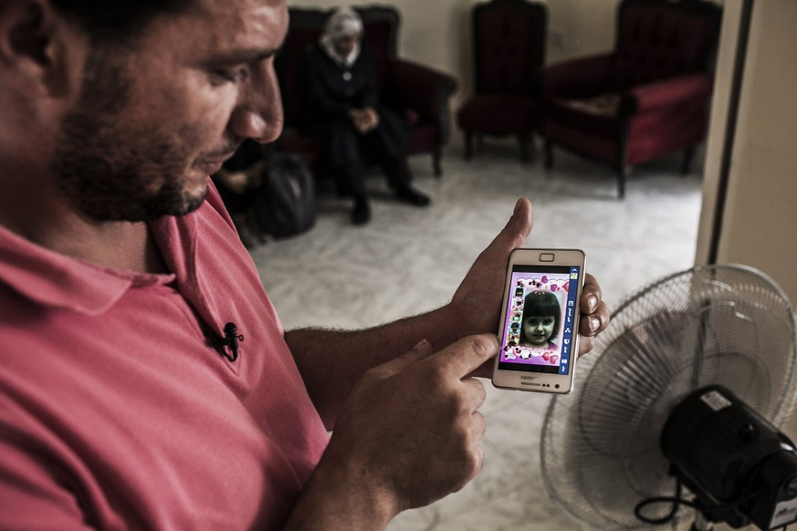In this image made available from the UNHCR on Monday Sept. 15, 2014 a Syrian refugee  in Valetta Saturday Sept. 13, 2014  shows an image of his young daughter who drowned while the vessel on which they fled their war torn country sank in the Mediterranean sea . The couple lost all of their three children in the accident. Since the start of 2014, more than 2,500 asylum seekers have perished trying to cross the Mediterranean. (AP Photo/Pete Muller/Prime for UNHCR)