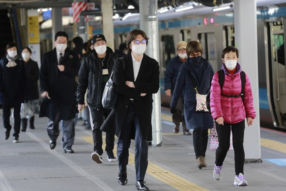 People wearing face masks to protect against the spread of the coronavirus walk at a platform at a train station in Tokyo, Monday, Feb. 1, 2021. (AP Photo/Koji Sasahara)