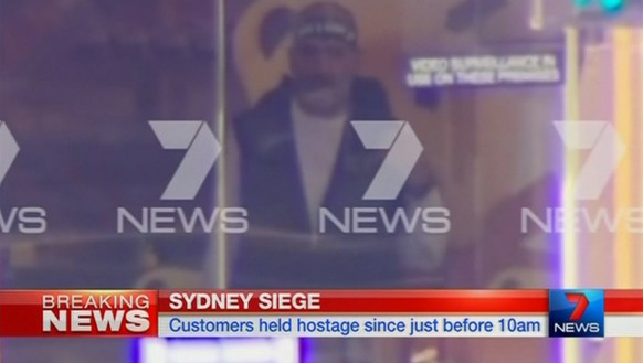 A man is seen standing behind the window of the Lindt cafe, where hostages are being held, in this still image taken from video from Australia's Seven Network on December 15, 2014. Dozens of hostages were trapped inside the central Sydney cafe on Monday, with local television showing some being forced to hold up a black flag with white Arabic writing in the window, raising fears of an attack linked to Islamic militants. REUTERS/Reuters TV via Seven Network/Courtesy Seven Network (AUSTRALIA - Tags: CIVIL UNREST CRIME LAW TPX IMAGES OF THE DAY)  ATTENTION EDITORS - THIS IMAGE HAS BEEN SUPPLIED BY A THIRD PARTY. IT IS DISTRIBUTED, EXACTLY AS RECEIVED BY REUTERS, AS A SERVICE TO CLIENTS. NO SALES. NO ARCHIVES. FOR EDITORIAL USE ONLY. NOT FOR SALE FOR MARKETING OR ADVERTISING CAMPAIGNS. AUSTRALIA OUT. NO COMMERCIAL OR EDITORIAL SALES IN AUSTRALIA. NO ACCESS AUSTRALIA / .COM.AU INTERNET SITES / ANY INTERNET SITE OF ANY AUSTRALIAN BASED MEDIA ORGANISATIONS / AUSTRALIAN NVO CLIENTS / SMH.COM.AU / NEWS.COM.AU