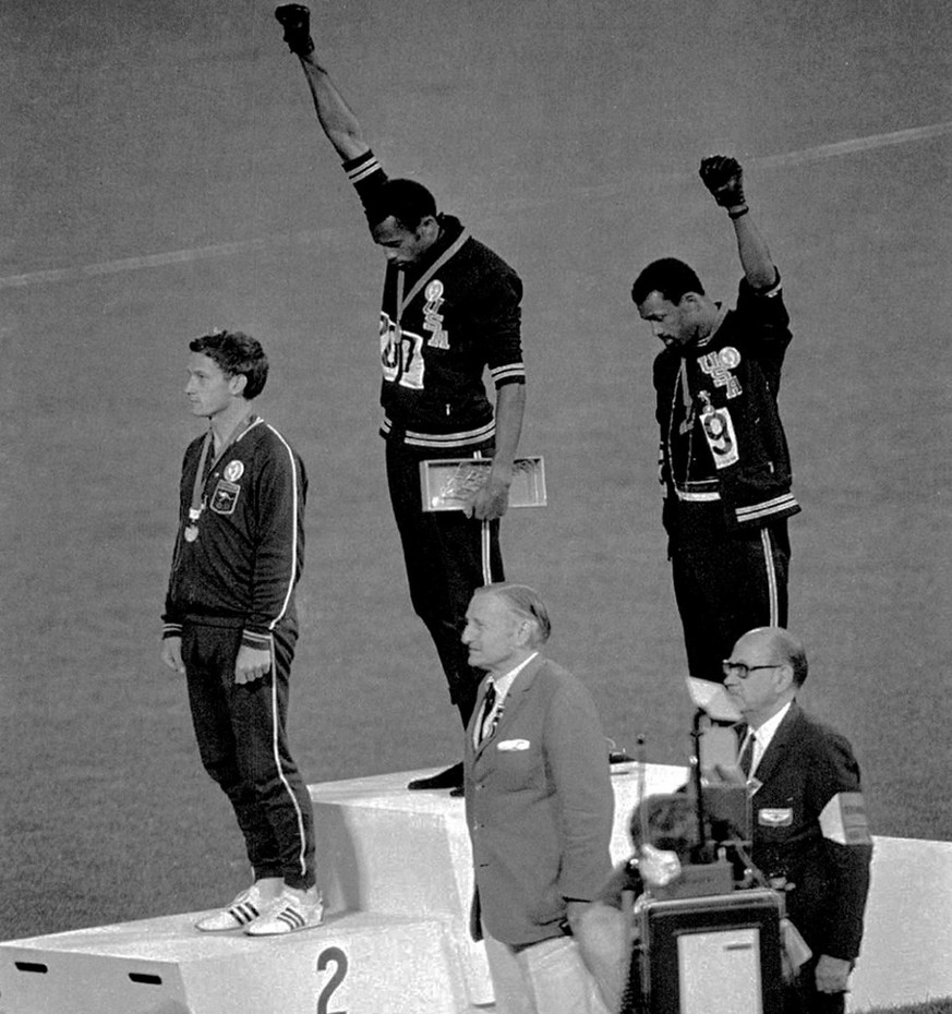 Extending gloved hands skyward in racial protest, U.S. athletes Tommie Smith, center, and John Carlos, stare downward October16, 1968 during the playing of the Star Spangled Banner after Smith received the gold and Carlos the bronze for the 200 meter run at the Olympics in Mexico City. Australian silver medalist Peter Norman is at left. (KEYSTONE/AP/Str)   [SIEHE IMAGE ID 1488048 / 98364346]