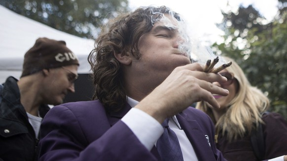FILE - In this Oct. 17, 2018, file photo, a man smokes multiple joints in a Toronto park as they mark the first day of legalization of cannabis across Canada. Supply shortages have been rampant in the two weeks since Canada became the largest national pot marketplace. (Chris Young/The Canadian Press via AP, File)