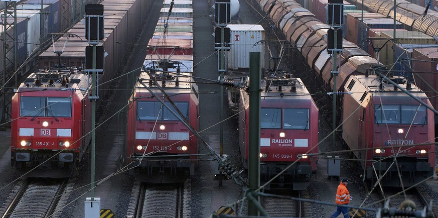 A worker passes parked locomotives in Europe's biggest marshalling yard in Maschen, near the northern German town of Hamburg in this March 10, 2011 file picture. German train drivers will stage a nationwide strike for the second time this week in a drawn-out dispute over pay and conditions with state-owned rail operator Deutsche Bahn, union GDL said on October 17, 2014. The strike by the drivers' union is due to start at 3 p.m.(1300 GMT) on October 17, 2014 for freight traffic and at 2 a.m. on October 18, 2014 for passenger trains. The walkout, which comes as school holidays start in many of Germany's federal states, is due to end on October 20 at 4 a.m. Picture taken March 10, 2011. REUTERS/Morris Macmatzen/Files (GERMANY  - Tags: BUSINESS CIVIL UNREST BUSINESS EMPLOYMENT TRANSPORT)