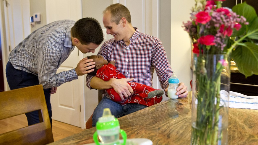 SOCIAL VALUES: Brooks Brunson kisses his son as his husband Gregg Pitts prepares to feed Thomas Brunson-Pitts, 6 months, a bottle in the morning before work at their home in Washington, on Thursday, May 19, 2016. Married in 2013, Brooks Brunson and Gregg Pitts always knew they wanted to have a family together, and were delighted when they were able to start the adoption process for their son shortly after beginning to look for a match in 2015. The child's birth mother had no problem with a same-sex couple adopting the baby.