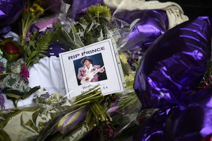 epa05272572 Fans leave flowers, photographs and balloons to a makeshift memorial under a star bearing Prince's name on an outside wall of First Avenue, the nightclub where Prince got his start, in Minneapolis, Minnesota, USA, 22 April 2016. US singer-songwriter and musician Prince died on 21 April at his residence in Chanhassen, Minnesota. He was 57.  EPA/CRAIG LASSIG