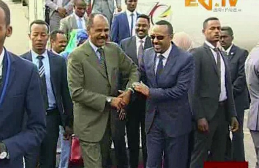 In this grab taken from video provided by ERITV, Ethiopia's Prime Minister Abiy Ahmed, centre right is welcomed by Erirea's President Isaias Afwerki as he disembarks the plane, in Asmara, Eritrea, Sunday, July 8, 2018. With laughter and hugs, the leaders of longtime rivals Ethiopia and Eritrea met for the first time in nearly two decades Sunday amid a rapid and dramatic diplomatic thaw aimed at ending one of Africa's longest-running conflicts. (ERITV via AP)