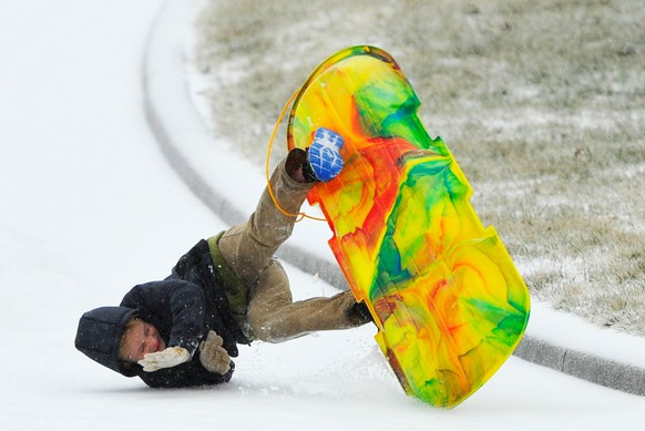 Nathan Moser flips as he sleds down an icy street covered by a winter storm that hit the Southeastern USA Monday, February 16, 2015 in Brentwood, Tennessee. The winter storm covered much of the Nashville area with up to one inch of sleet and freezing rain, canceling schools and closing businesses. REUTERS/Harrison McClary  (UNITED STATES - Tags: ENVIRONMENT SOCIETY)