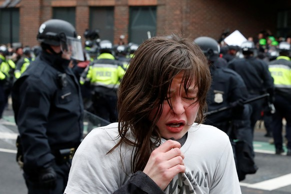 An activist demonstrating against U.S. President Donald Trump reacts after being hit by pepper spray on the sidelines of the inauguration in Washington, DC, U.S., January 20, 2017. REUTERS/Adrees Latif     TPX IMAGES OF THE DAY