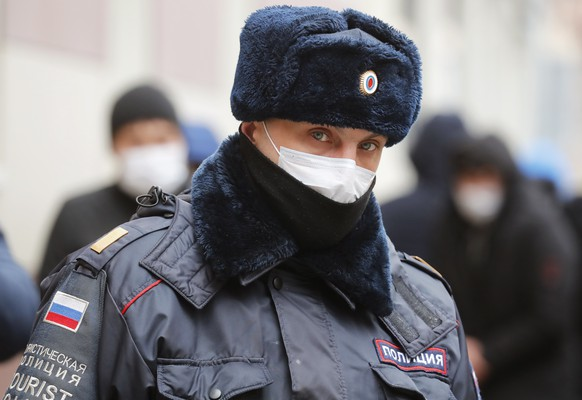 epa08340673 A Russian police officer wearing a protective face mask stands outside a migration control centre amid the ongoing coronavirus COVID-19 pandemic in St. Petersburg, Russia, 03 April 2020. Russia is granting additional 90 days to all foreign nationals who are staying in Russia on visa during the pandemic, regardless of the purpose of their visit.  EPA/ANATOLY MALTSEV