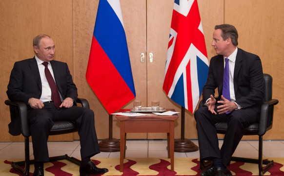 Britain's Prime Minister David Cameron (R) talks with Russian President Vladimir Putin at a meeting at Charles De Gaulle Airport in Paris, France June 5, 2014.   REUTERS/Stefan Rousseau/Pool    (FRANCE - Tags: POLITICS)
