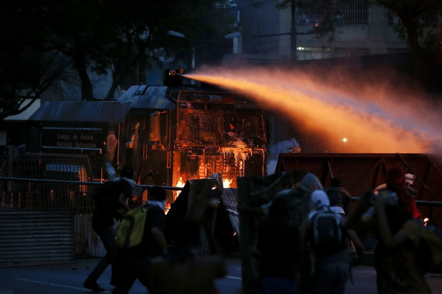 A water canon batters down a barricade set up by anti-government protesters during riots in Caracas April 20, 2014. Masked youths battled police, protesters burned and hung from lamp-posts effigies of President Nicolas Maduro and marchers demanded the