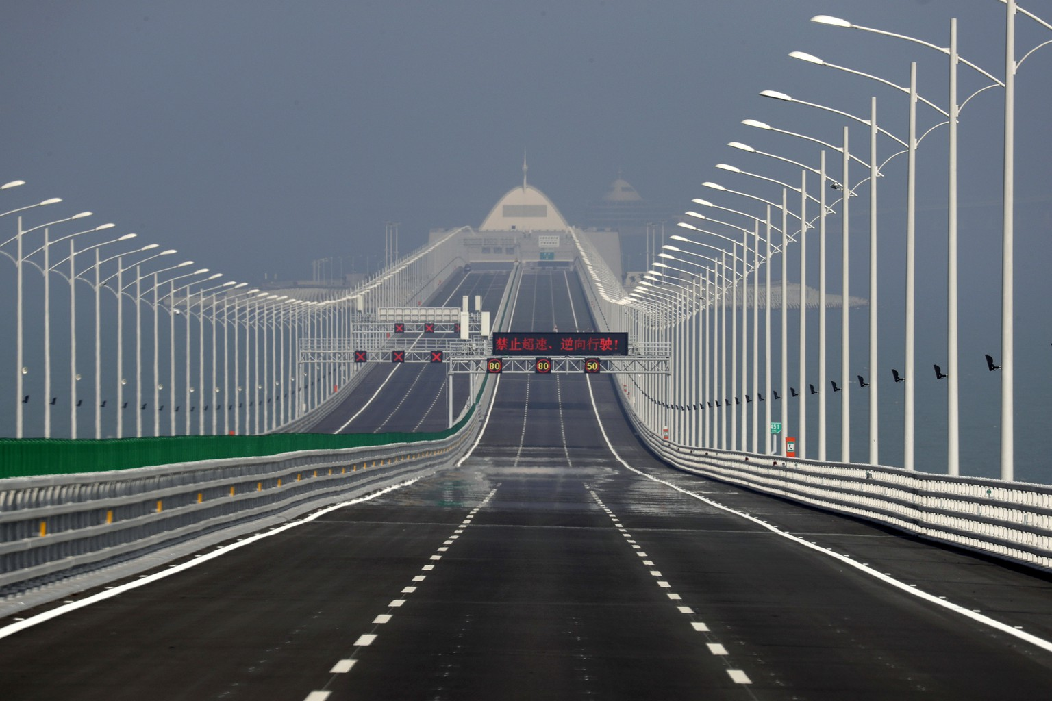 The Hong Kong-Zhuhai-Macau Bridge is seen, in Zhuhai city, south China's Guangdong province, Wednesday, March 28, 2018. The Hong Kong-Zhuhai-Macau Bridge, the world's longest cross-sea project, which has a total length of 55 kilometers. The main section includes 23 kilometers of bridges, 6.7 kilometers of tunnels, and two artificial islands. (AP Photo/Kin Cheung)