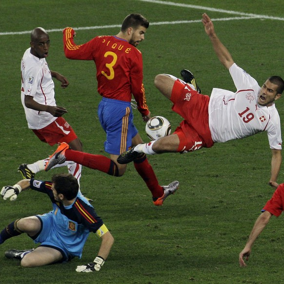 Switzerland's Eren Derdiyok, center, Spain's Gerard Pique, second from left at top, and Spain goalkeeper Iker Casillas, bottom left, vie for the ball during the World Cup group H soccer match between Spain and Switzerland at the stadium in Durban, South Africa, Wednesday, June 16, 2010.  (AP Photo/Roberto Candia)