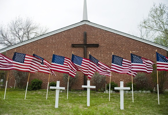 epa04153179 US national flags and crosses representing victims of the shooting at Fort Hood military base are displayed outside Central Christian Church in Killeen, Texas, USA, 03 April 2014. The gunman suspected of killing three people and wounding 16 at Fort Hood, Texas, before taking his own life may have had an argument with other soldiers 'immediately' preceding the shooting spree, the base commander said 03 April. Lieutenant General Mark Milley said that the victims seemed to have been shot at random in 02 April afternoon's rampage by Army Specialist Ivan Lopez, 34.  EPA/ASHLEY LANDIS