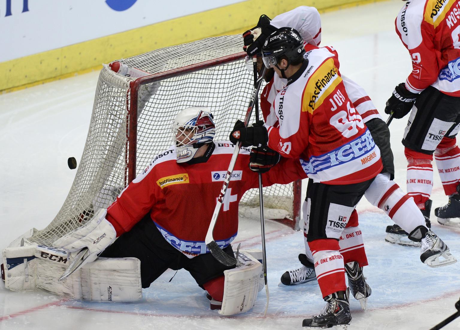 Switzerland's goalkeeper Reto Berra, left, and Roman Josi, right, fight for the puck with Canada's Joel Ward, center, during a friendly ice hockey match Switzerland versus Canada, on Tuesday, May 6, 2014, in the Hallenstadion in Zuerich, Switzerland. Both teams prepare for the upcoming 2014 Ice hockey World Championships in Belorussia. (KEYSTONE/Steffen Schmidt)