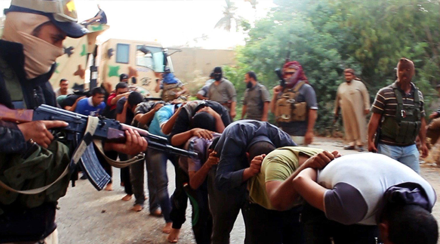This image posted on a militant website on Saturday, June 14, 2014, which has been verified and is consistent with other AP reporting, appears to show militants from the al-Qaida-inspired Islamic State of Iraq and the Levant (ISIL) leading away captured Iraqi soldiers dressed in plain clothes after taking over a base in Tikrit, Iraq. The Islamic militant group that seized much of northern Iraq has posted photos that appear to show its fighters shooting dead dozens of captured Iraqi soldiers in a province north of the capital Baghdad. Iraq's top military spokesman Lt. Gen. Qassim al-Moussawi confirmed the photos' authenticity on Sunday and said he was aware of cases of mass murder of Iraqi soldiers. (AP Photo via militant website)