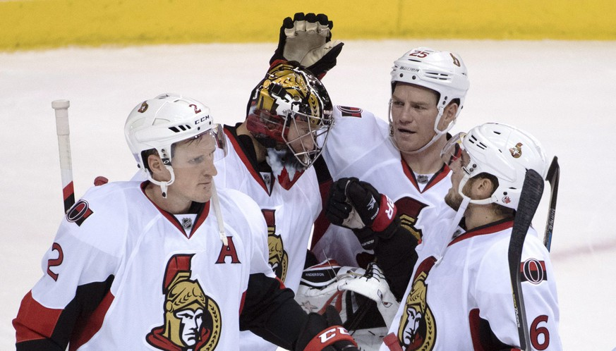 Ottawa Senators' Dion Phaneuf (2), left to right, goalie Craig Anderson (41), Chris Neil (25) and Chris Wideman (6) celebrate their victory over the Vancouver Canucks following the third period of an NHL hockey game, Tuesday, Oct. 25, 2016 in Vancouver, British Columbia.  (Jonathan Hayward/The Canadian Press via AP)